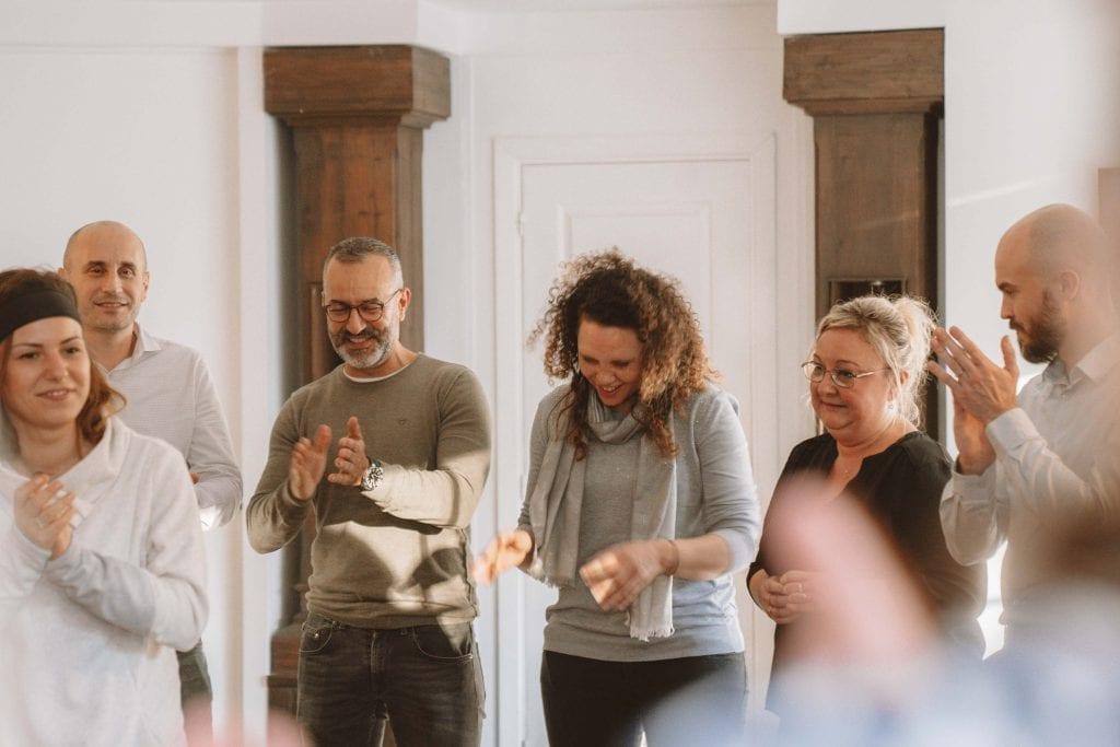 Un groupe de personnes rigolant et applaudissant lors d'une animation team-building