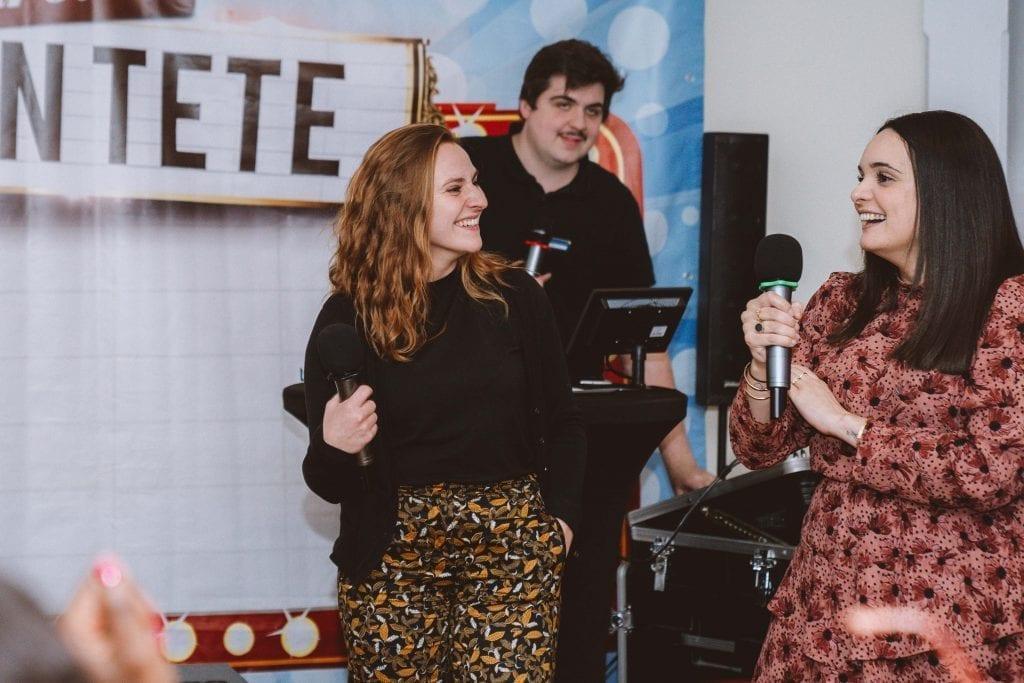 Deux femmes tenant des micros, participant à une animation team-building