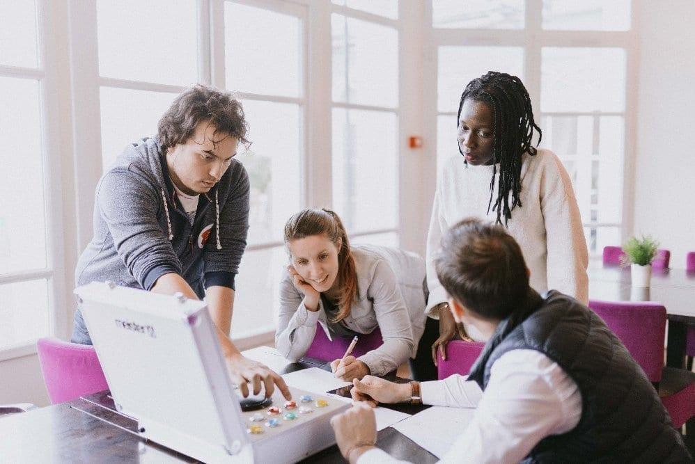 Groupe de séminaristes réfléchissant autour d'une table lors d'une animation teambuilding