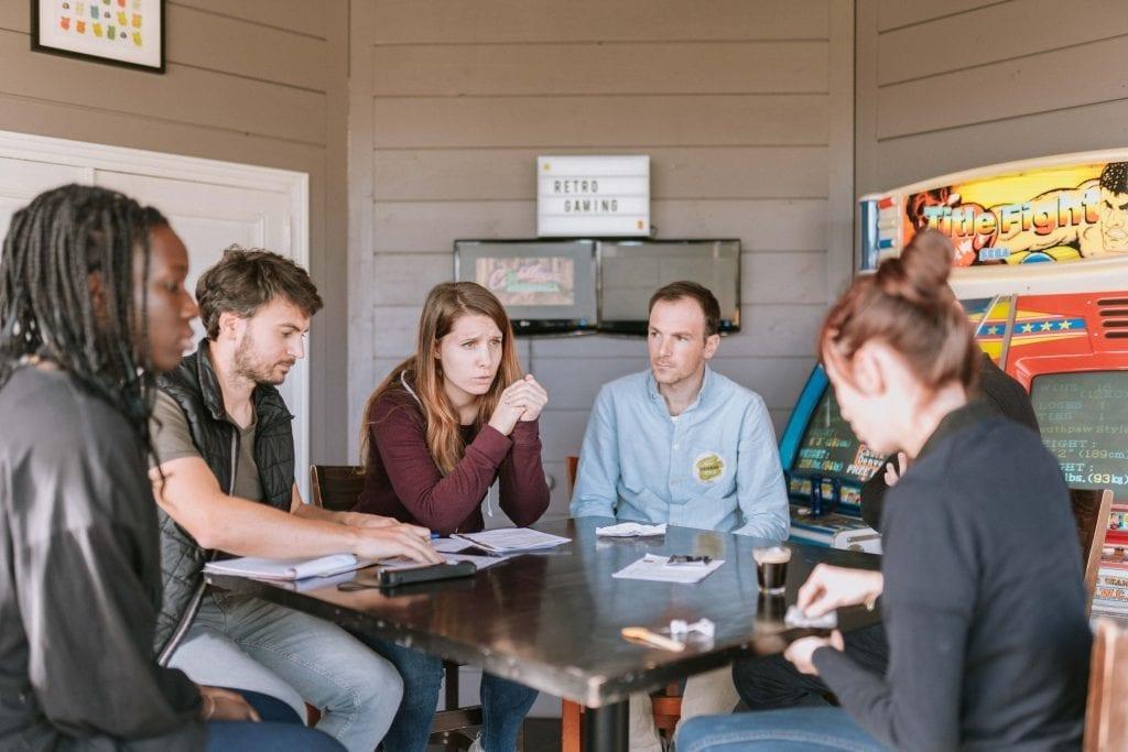 Un groupe de personnes autour d'une table, interrogeant une autre personne lors d'une animation team-building