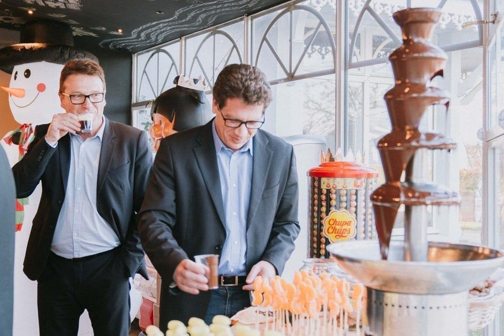 Une personne mangeant des fruits avec une fontaine au chocolat au premier plan et une personne buvant un café