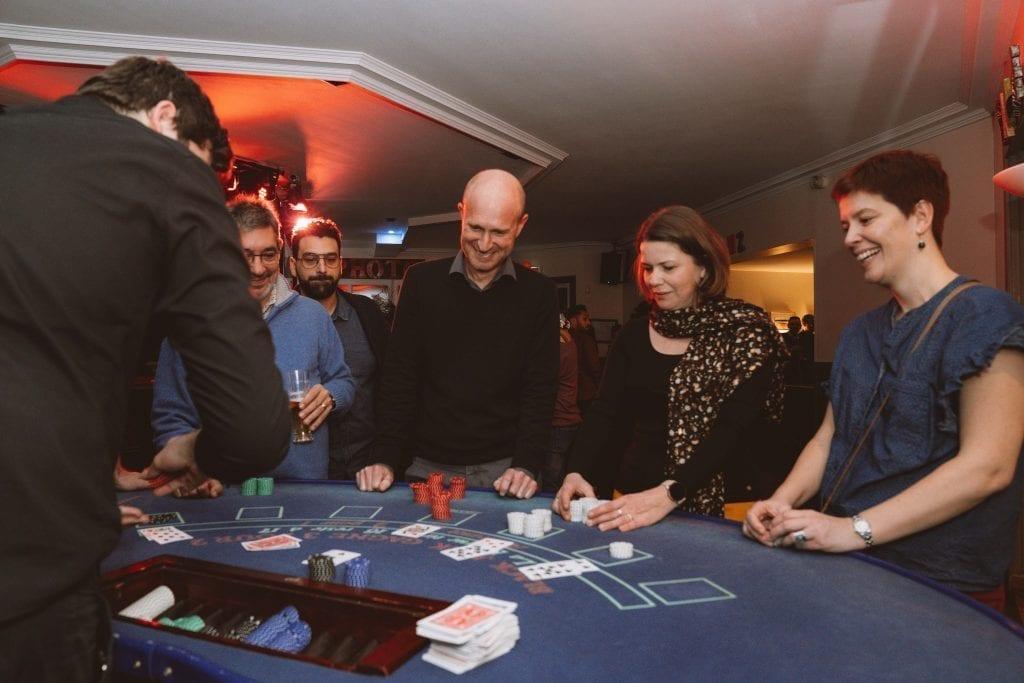 Un groupe de personne jouant au blackjack autour d'une table de casino