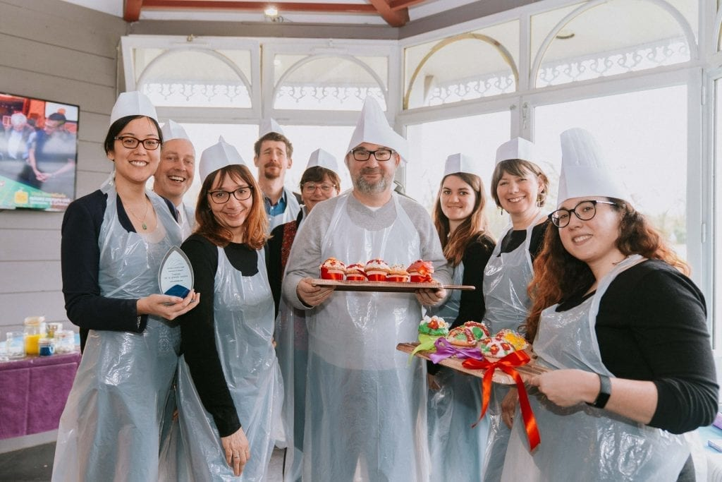 Les participants d'une animation team-building montrant leurs cupcakes décorés et leur trophée
